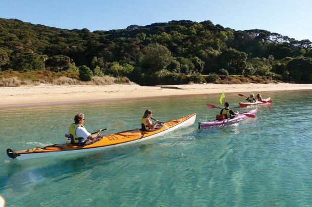 Quietly gliding on perfectly still waters kayakers enjoy the Bay of Islands.