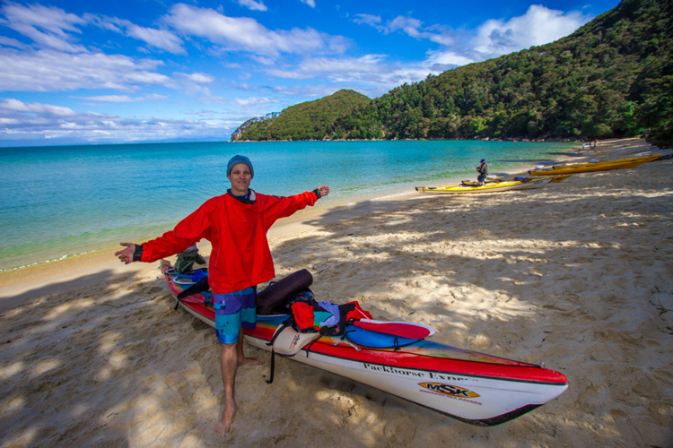 A kayaker having finished paddling for the day rests on the shores of Abel Tasman.