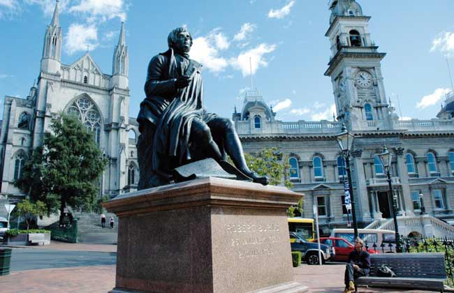 A large statue of Robert Burns in front of a grand cathedral.