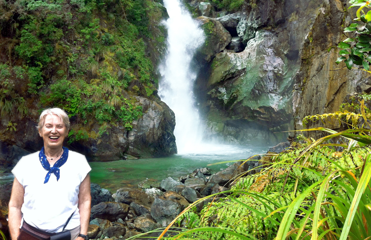 Hiker enjoying one of the many waterfalls - Hollyford Track