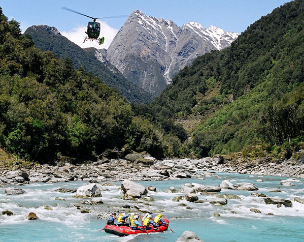 Afder delivering the rafters safely the helicopter soars into the distance leaving those behind to experience the best rafting in New Zealand.
