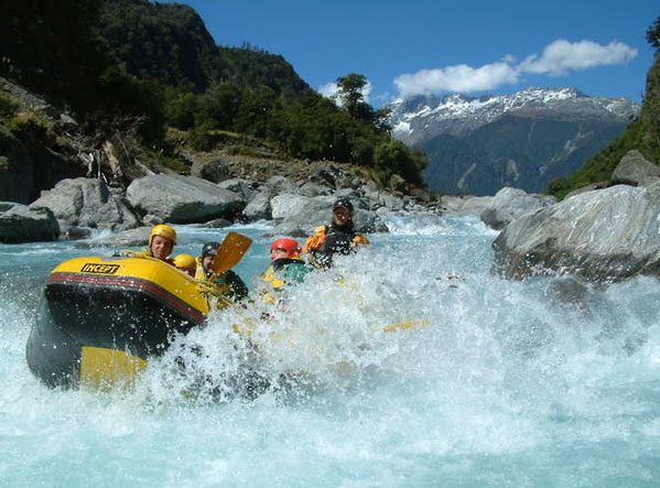 With towering mountains in the background the rafters enjoy a soaking as they traverse the Hokitika river.