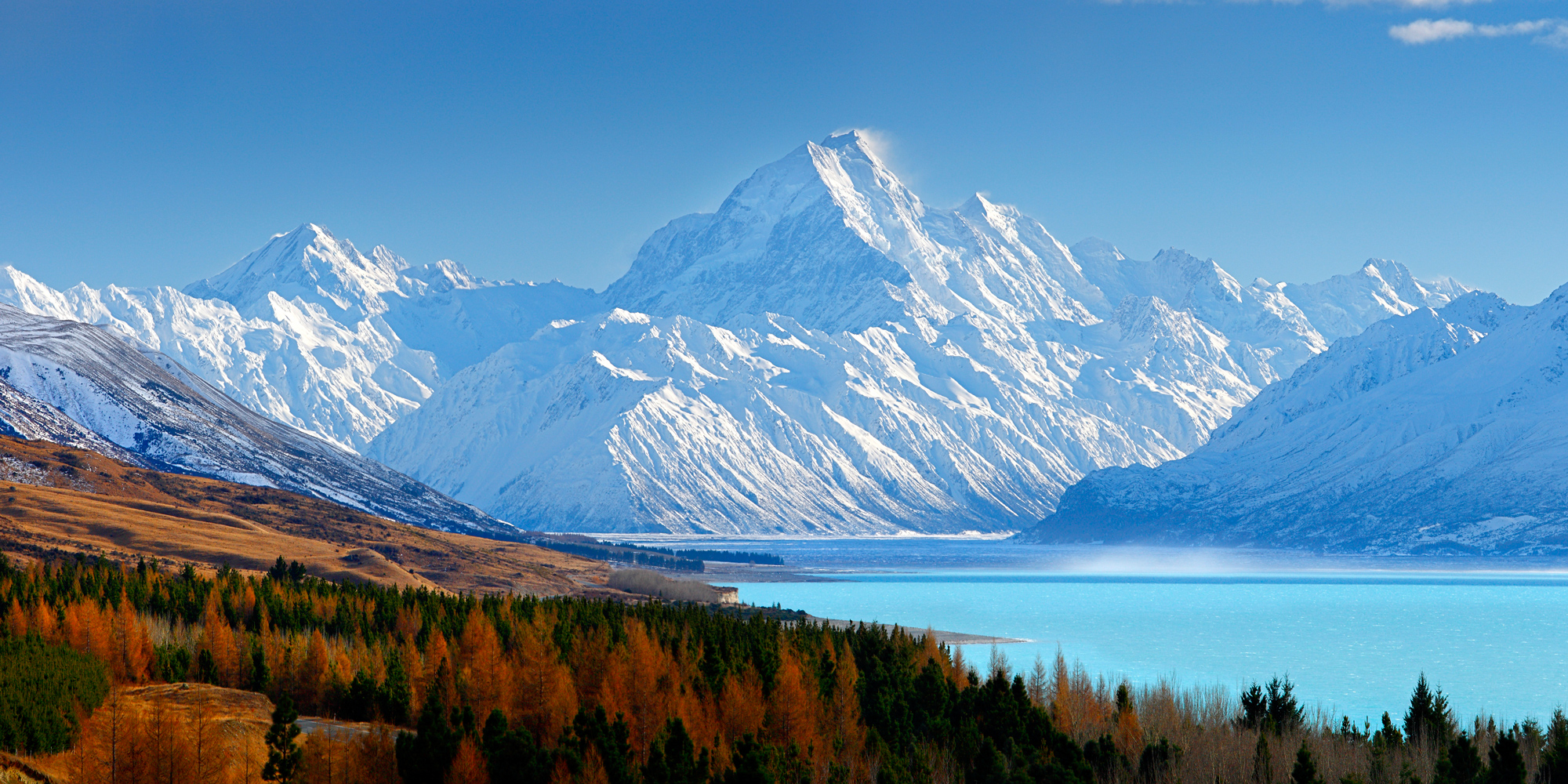 A bright blue turquoise lake with autumnal trees on one side, and a huge snow covered mountain in the distance