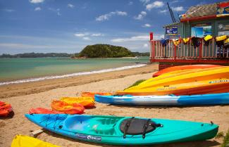 Kayaks sitting on Paihia beach.