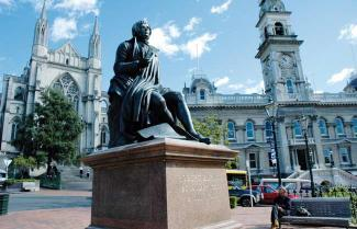 Dunedin City with a statue of Robbie Burns ot front.