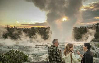 couple standing next to a geyser in Rotorua
