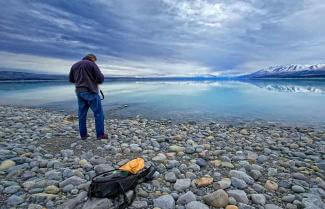 Man taking photo of beautiful Lake Tekapo New Zealand